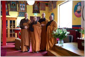 Quatre monastiques en robe marron et orange dans un temple tibétain