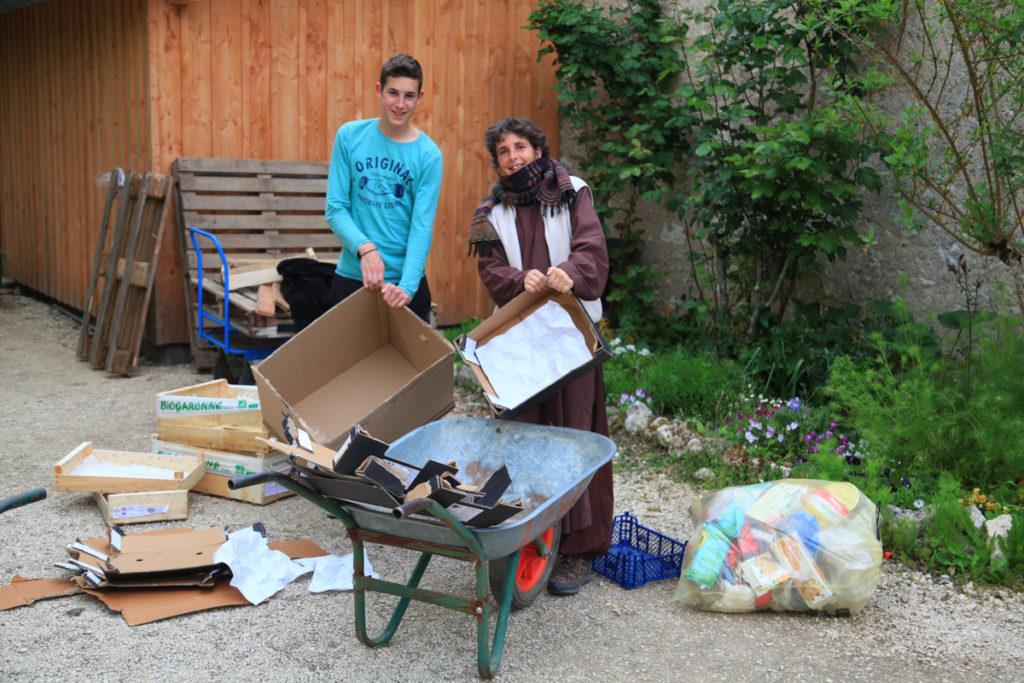 Une amie et son fils sont debout devant une brouette et ils déplient des cartons pour les recycler